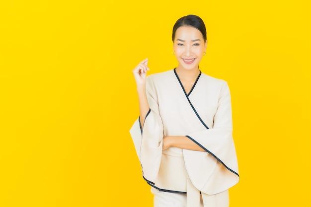 Retrato de joven y bella mujer asiática de negocios sonriendo con traje blanco en la pared amarilla