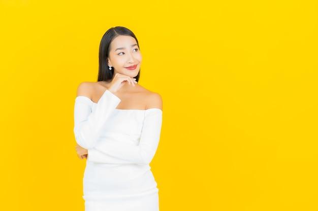 Retrato de joven y bella mujer asiática de negocios sonriendo con vestido blanco en la pared amarilla