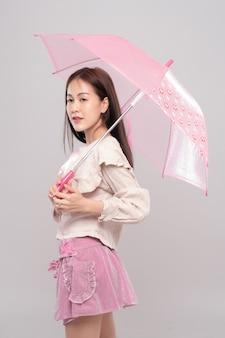 Retrato de joven bella mujer asiática con paraguas, pensando