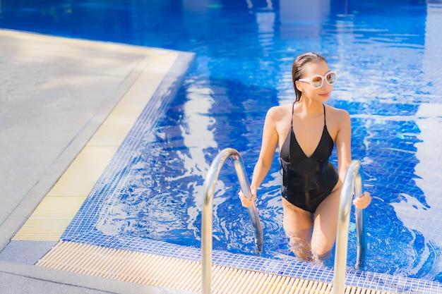 Retrato de joven y bella mujer asiática relajándose alrededor de la piscina al aire libre en el hotel resort