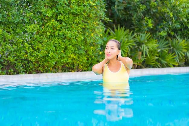 Retrato de joven y bella mujer asiática relajándose en la piscina