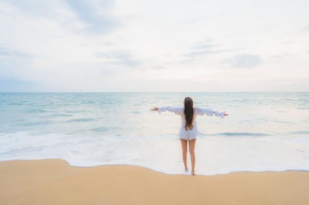 Retrato de joven y bella mujer asiática relajándose en la playa al aire libre en viajes de vacaciones