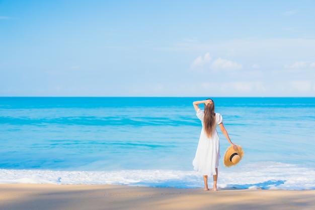 Retrato de joven y bella mujer asiática relajándose en la playa con nubes blancas en el cielo azul en viajes de vacaciones