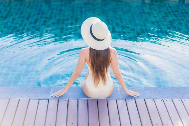 Retrato de joven y bella mujer asiática relajante alrededor de la piscina al aire libre en el hotel resort