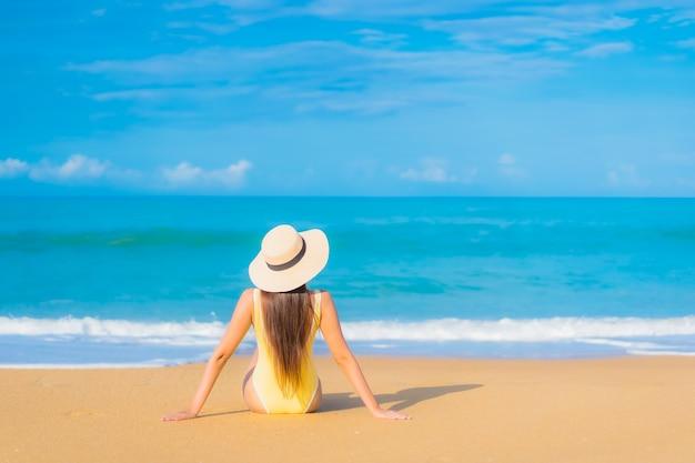 Retrato de joven y bella mujer asiática relajante en la playa en vacaciones de viaje