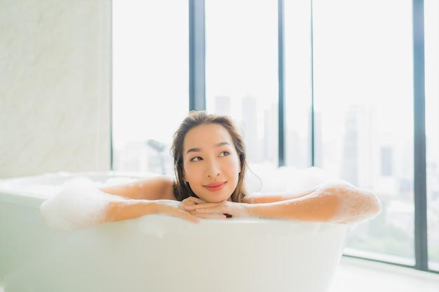 Retrato joven y bella mujer asiática relajarse y descansar en la bañera