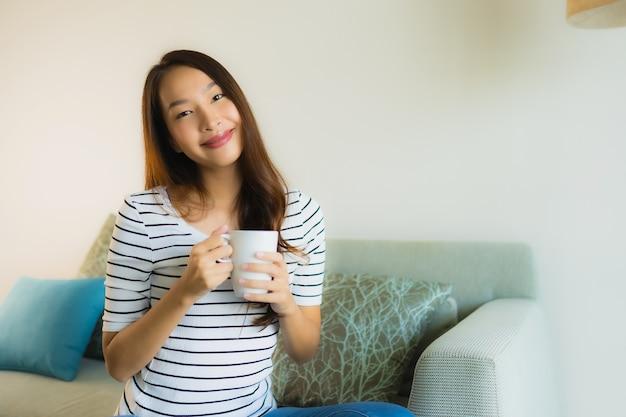 Retrato joven y bella mujer asiática en el sofá con una taza de café