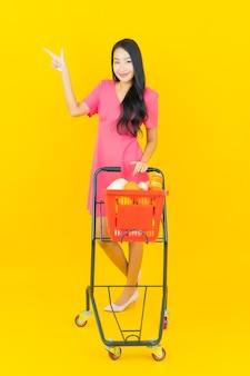 Retrato joven y bella mujer asiática sonríe con la cesta de la compra del supermercado en la pared amarilla