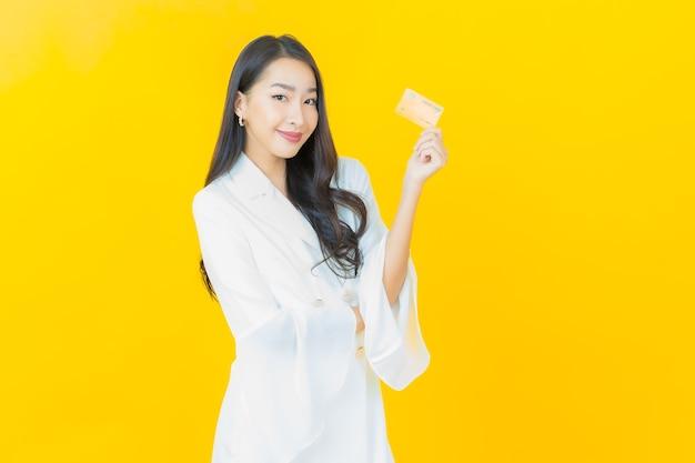 Retrato de joven y bella mujer asiática sonríe con tarjeta de crédito en la pared amarilla