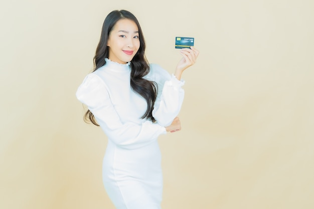 Retrato de joven y bella mujer asiática sonríe con tarjeta de crédito en la pared de color