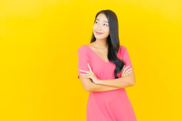 Retrato de joven y bella mujer asiática sonríe en vestido rosa en la pared amarilla
