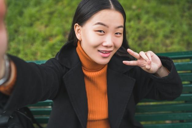 Retrato de joven bella mujer asiática tomando un selfie mientras está sentado en un banco en el parque al aire libre.