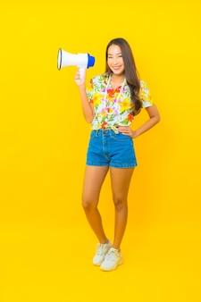 Retrato de joven y bella mujer asiática utiliza megáfono para comunicarse en la pared amarilla