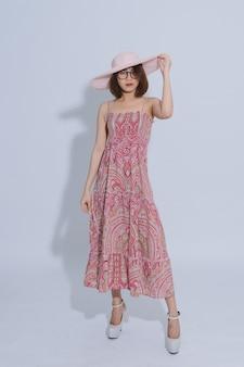 Retrato de una joven y bella mujer asiática con un vestido largo en un sombrero posando. chica asiática pelo corto con gafas y sombrero rosa en estudio.
