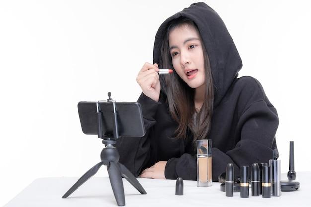 Retrato de joven y bella mujer asiática vlogger de belleza haciendo maquillaje mirando en la cámara blogger grabando y transmitiendo video para compartir en las redes sociales