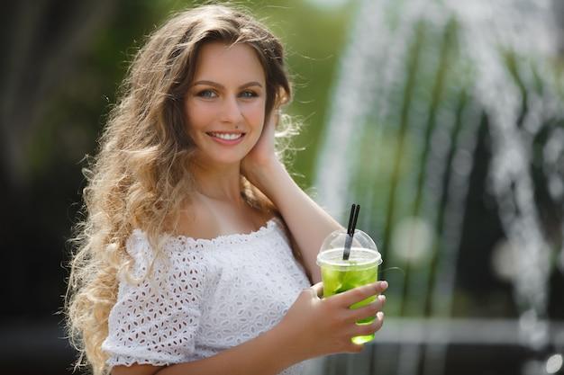 Retrato de una joven y bella mujer atractiva al aire libre en verano con un vaso de jugo o bebida helada. linda chica afuera con mojito fresco