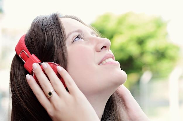 Retrato de joven bella mujer con auriculares rojos escuchando música