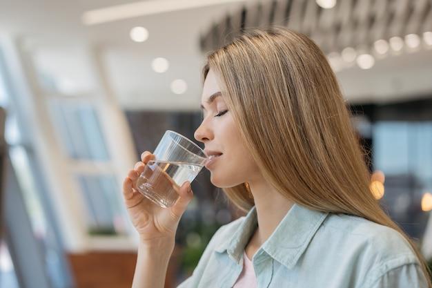 Retrato de joven bella mujer bebiendo agua en casa. concepto de estilo de vida saludable