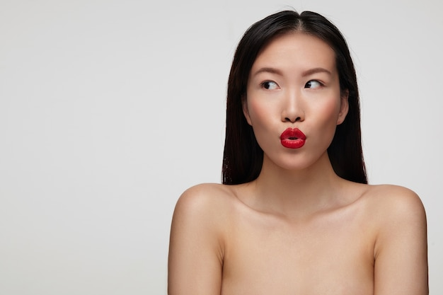 Retrato de joven y bella mujer de cabello oscuro con peinado casual doblando sus labios mientras mira con asombro a un lado, de pie sobre la pared blanca