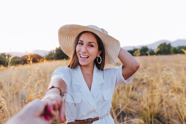 Retrato de joven bella mujer caucásica al aire libre al atardecer en un campo amarillo. vistiendo un sombrero moderno y sonriendo. tomados de la mano, sígueme concepto