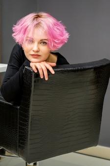 Retrato de una joven y bella mujer caucásica con nuevo peinado rosa corto sentado en una silla en un salón de belleza