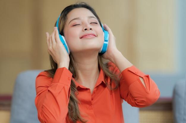 Retrato de joven bella mujer disfrutando de la música con rostro sonriente sentado junto a la ventana en la oficina creativa o cafetería
