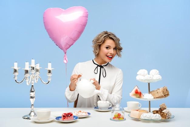 Retrato de joven bella mujer con dulces sobre pared azul