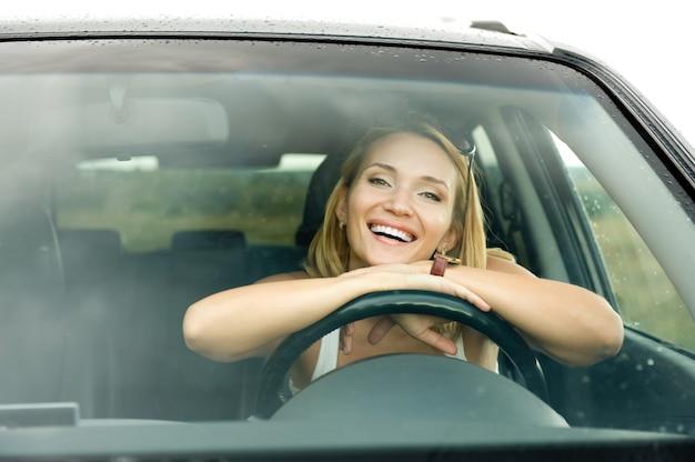 Retrato de joven y bella mujer feliz en el coche nuevo - al aire libre