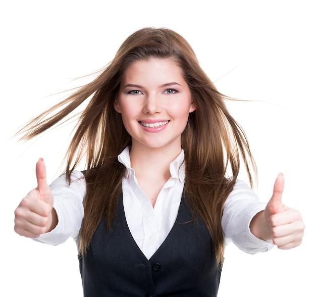 Retrato de una joven y bella mujer feliz con pulgares arriba signo sobre pared blanca.