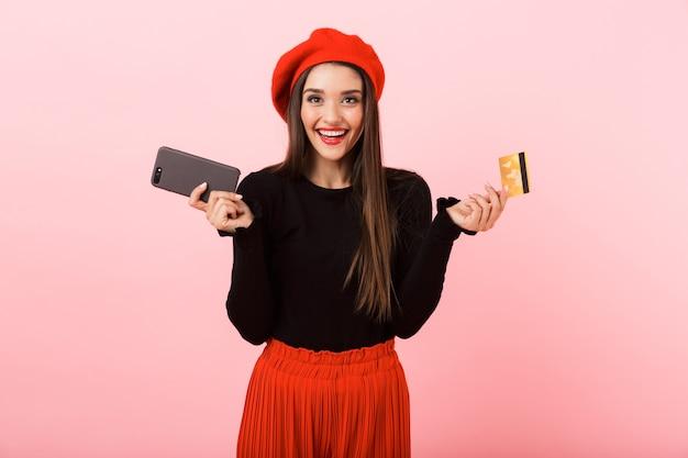 Retrato de una joven y bella mujer feliz vistiendo boina roja que se encuentran aisladas sobre fondo rosa, sosteniendo un teléfono móvil y una tarjeta de crédito de plástico