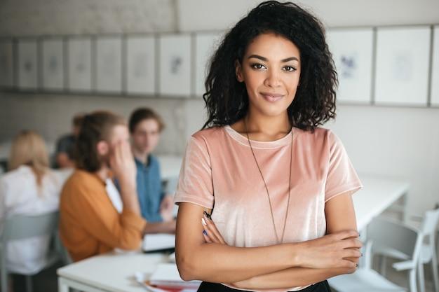 Retrato de joven bella mujer felizmente mirando al frente en el aula con estudiantes