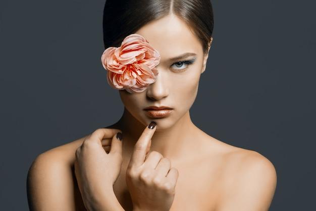 Retrato de joven bella mujer con una flor en el ojo