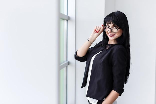 Retrato de joven bella mujer con gafas de pie cerca de la ventana
