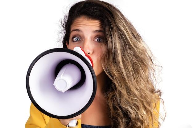 Retrato de joven bella mujer gritando en un megáfono aislado en la pared blanca. concepto de marketing o ventas.