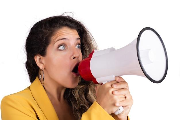 Retrato de joven bella mujer gritando en un megáfono aislado sobre fondo blanco. concepto de marketing o ventas.