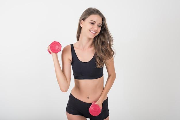 Retrato de joven bella mujer haciendo ejercicios físicos con pesas
