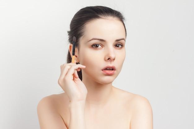 Retrato de joven bella mujer haciendo pincel de maquillaje