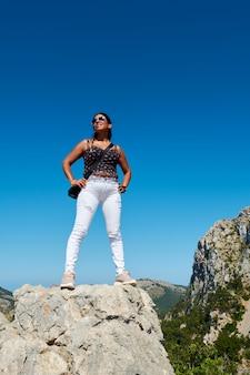 Retrato de una joven y bella mujer latina hispana, haciendo la posición de conquista superior, en el acantilado de la montaña, cabo formentor, mallorca
