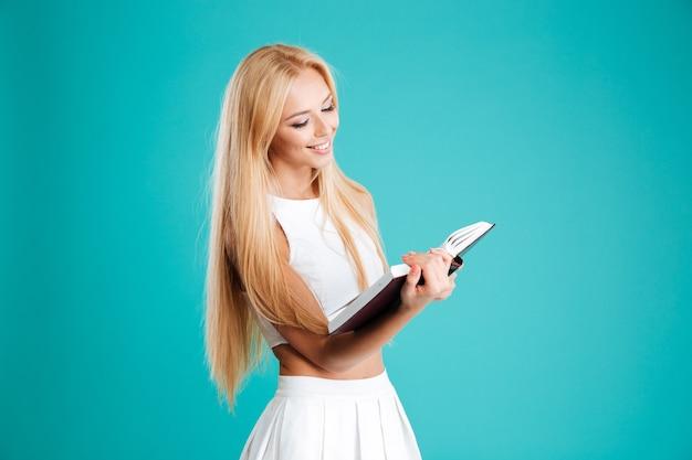 Retrato de una joven y bella mujer leyendo un libro aislado en el fondo azul.