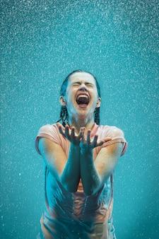 Retrato de joven bella mujer bajo la lluvia