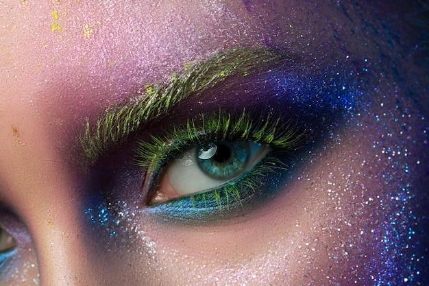 Retrato de joven bella mujer con maquillaje creativo de moda moderna. maquillaje de pasarela o halloween. tiro del estudio. ojo de cerca.