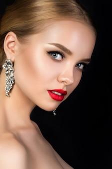 Retrato de joven bella mujer con maquillaje de noche mirando por encima del hombro.