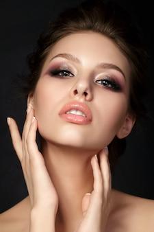 Retrato de joven bella mujer con maquillaje de noche tocando su rostro sobre fondo negro. ojos ahumados multicolores