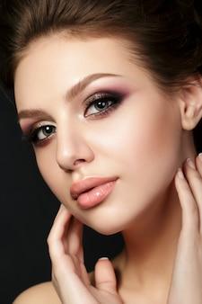 Retrato de joven bella mujer con maquillaje de noche tocando su rostro sobre fondo negro.