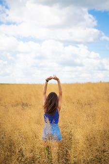 Retrato de una joven y bella mujer morena con una camiseta azul y pantalones cortos de mezclilla se encuentra en medio del campo, exponiendo su rostro al sol