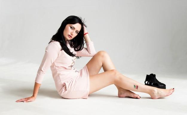 Retrato de una joven y bella mujer morena con un vestido rosa sentada en el suelo