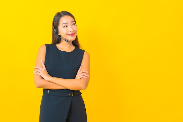 Retrato joven y bella mujer de negocios asiática con atención al cliente del centro de llamadas de auriculares sobre fondo amarillo