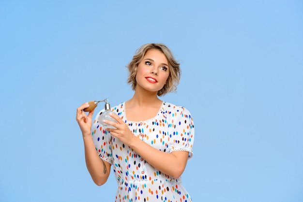Retrato de joven bella mujer con perfume sobre pared azul