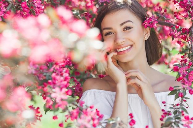 Retrato de joven bella mujer con piel suave perfecta de cerca. señora atractiva en flores. retrato facial de mujer hermosa.