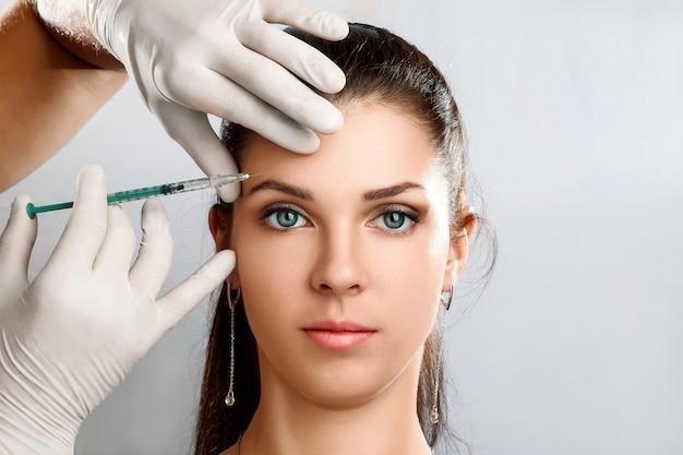 Retrato de una joven y bella mujer recibiendo inyección cosmética de botox